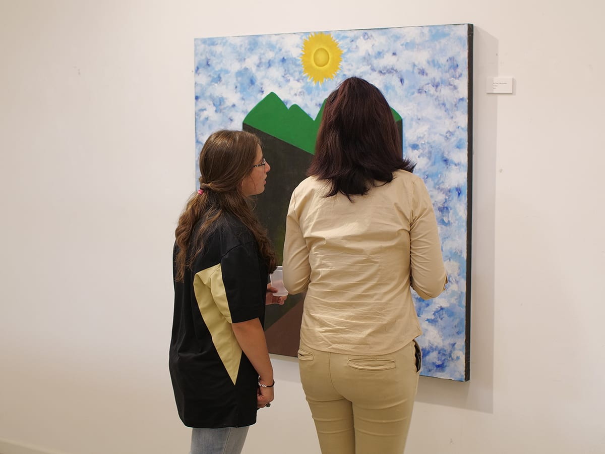 Two people looking at art on wall